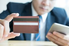 Male holding a credit card and using smart mobile phone for onli Royalty Free Stock Photography