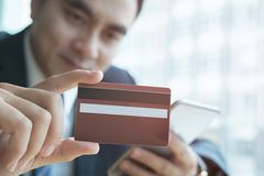 Male holding a credit card and using smart mobile phone for onli Stock Images
