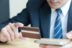 Male holding a credit card and using smart mobile phone for onli Royalty Free Stock Images