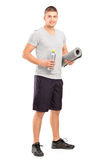 Male holding drink and mat after an exercise. Full length portrait of a male holding a bottle of refreshment drink and a mat after an exercise  on white Stock Photos