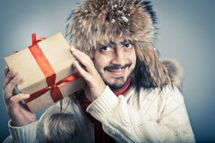 Male holding a gift. Positive male in fur hat shaking a gift box and smiling. Winter and christmas concept Stock Images