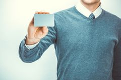 Male holding in hand blank card of grey color in one hand. Close up studio shot Stock Images