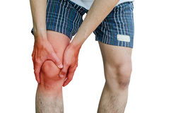 Male holding hand to spot of knee-aches Stock Photo