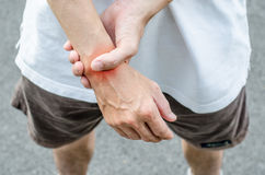 Male holding hand to spot of wrist pain. Stock Photos
