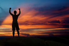 Male holding hand up and expressing gladness. Positive male holding hand up and expressing gladness while standing on stone in Sunset stock photo