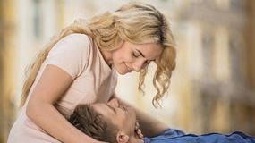 Male holding head on girls lap, girlfriend hugging guy, romantic relationship. Stock video Royalty Free Stock Photo
