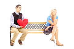Male holding a red heart and disappointed female sitting Stock Images
