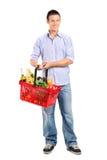 Male holding a shopping basket. Full length portrait of a young male holding a full shopping basket  on white background Stock Image
