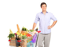 A male holding a shopping cart with groceries. A young male holding a shopping cart full with groceries isolated on white background Royalty Free Stock Images