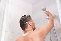 Male holding shower head with flowing water. In shower cabin with transparent glass doors in the modern tiled bathroom Royalty Free Stock Photos