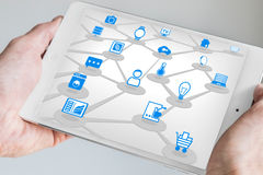 Male holding tablet in both hands with internet of everything (IOT) concept. Connected devices like sensors and smart phone Royalty Free Stock Image