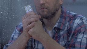 Male holding tablets and looking to rainy window, drug side effect, disease. Stock footage stock video