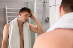 Male holding towel on his shoulders while correcting hair. Male holding towel on his shoulders after washing procedures while correcting hair standing in the Royalty Free Stock Photography