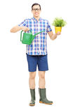 Male holding a watering can and flower pot Royalty Free Stock Photos