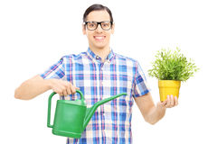 Male holding a watering can and flower pot Royalty Free Stock Photography