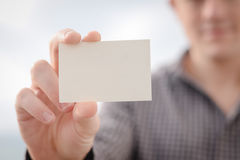 Male holding white business card on light Royalty Free Stock Images