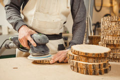 Male holding wooden round workpiece and processing with grinding machine Stock Photography