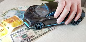 Male holds in his fingers Black Bugatti Chiron metal toy standing with front wheels on paper dolla royalty free stock images