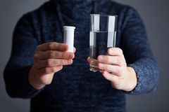 Male holds pills ready to dissolve one in water stock photo