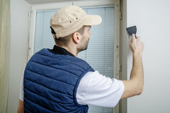 Male holds putty knife on the wall near the wall corner. Finishing work Stock Images