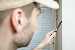 Male holds putty knife on the wall near the wall corner. Finishing work Royalty Free Stock Photos