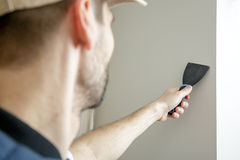 Male holds putty knife on the wall near the wall corner. Finishing work Stock Photos