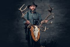 Male holds a skull of a deer. The bearded hunter male holds a skull of a deer Stock Photos