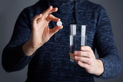 Male holds a tablet ready to dissolve the pill in water stock images