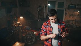 Male in the home garage on the background of shelves with tools and machines uses the caliper. Man in the home garage on the background of shelves with tools and stock video