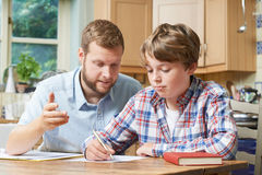 Male Home Tutor Helping Boy With Studies. Male Home Tutor Helps Boy With Studies Stock Photos
