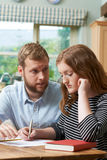 Male Home Tutor Helping Girl Struggling With Studies. Male Home Tutor Helps Girl Struggling With Studies Royalty Free Stock Images