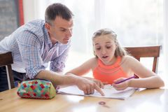 Male Home Tutor Helping Teenage Girl With Studies. A Male Home Tutor Helping Teenage Girl With Studies royalty free stock photography