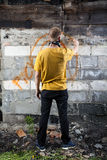 Male hooligan painting graffiti. Vertical view of male hooligan painting graffiti Stock Photo