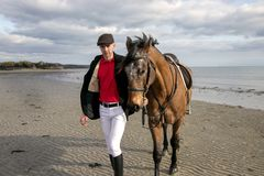 Handsome man, Male Horse Rider walking with his horse on beach, wearing traditional flat cap, white trousers, red polo shirt. Male horse rider, walks with his Stock Image