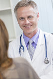 Male Hospital Doctor Talking to Female Patient Stock Photos