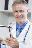 Male Hospital Doctor Using Tablet Computer. Male medical doctor using a white tablet computer in a hospital office Royalty Free Stock Photos