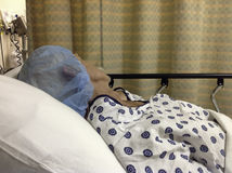 Male hospital patient before surgery wearing cap. Older man wearing hospital gown and blue cap lies in hospital bed awaiting surgery. Curtain is in the royalty free stock images
