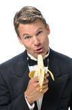 Male host singing with banana. Portrait of handsome male Caucasian host in black tuxedo singing into a banana microphone with white background Stock Photography