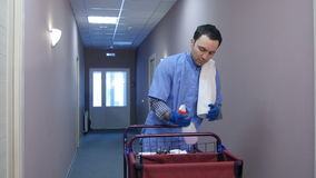 Male hotel cleaner putting on gloves before cleaning the room stock footage