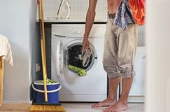 Male housewife or bachelor concept. Young man loads the laundry into the washing machine stock images