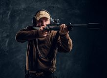 Male hunter in cap and headphones holding a rifle and aiming at his target or prey. Studio photo against a dark wall royalty free stock photography
