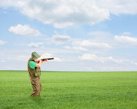 Male hunter shooting with a rifle outside in a field Royalty Free Stock Image