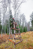 Male hunter at watch tower in autumn forest Baltic. Male hunter at watch tower in autumn forest in Latvia, Baltic country Royalty Free Stock Images
