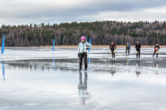 Male ice skater with pink helmet and four skaters in the background. Stock Photos