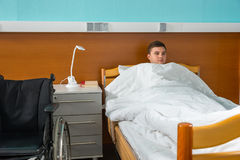 Male ill patient lying in the hospital bed covered with quilt in Royalty Free Stock Photos