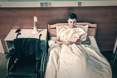Male ill patient lying in the hospital bed and reading a book in. Hospital ward. Healthcare concept Stock Photography