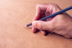 Male illustrator and sketch artist drawing with pencil. Hand close up with selective focus Stock Photos