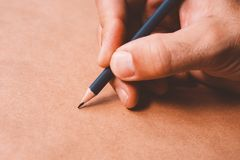 Male illustrator and sketch artist drawing with pencil. Hand close up with selective focus Stock Photography