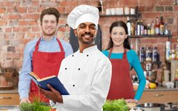 Male indian chef reading cookbook at cooking class stock photography