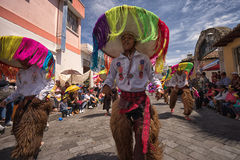 Male indigenous dancers wearing chaps. June 17, 2017 Pujili, Ecuador: male indigenous dancers in chaps wearing large hats dancing in the street at Corpus Christi stock photography
